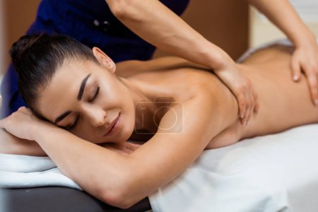 beautiful smiling young woman with closed eyes enjoying massage in spa