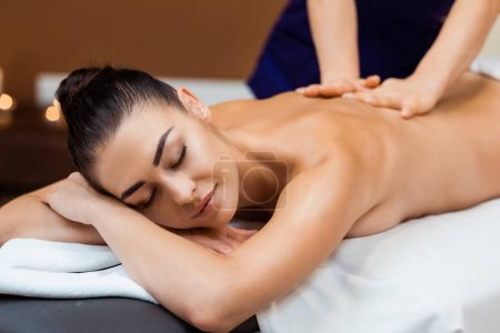 Photo for Attractive smiling young woman with closed eyes enjoying massage in spa - Royalty Free Image