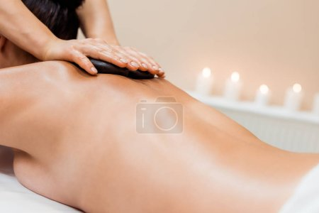 partial view of young woman having hot stone massage in spa salon
