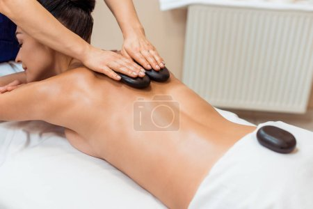 attractive young woman having hot stone massage in spa salon