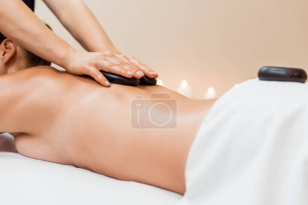 cropped shot of young woman having hot stone massage in spa salon