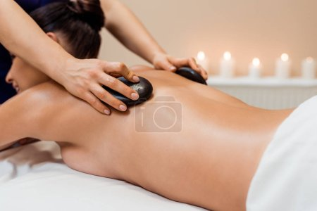 cropped shot of young woman having hot stone massage in spa