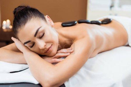Photo pour Belle fille souriante bénéficiant d'un massage aux pierres chaudes dans le salon de spa - image libre de droit