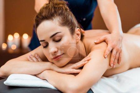 hermosa joven sonriente con los ojos cerrados teniendo masaje en el salón de spa