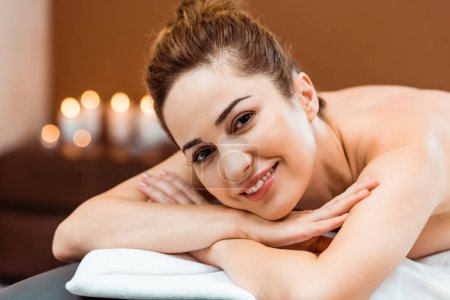 beautiful happy young woman lying on massage table and smiling at camera