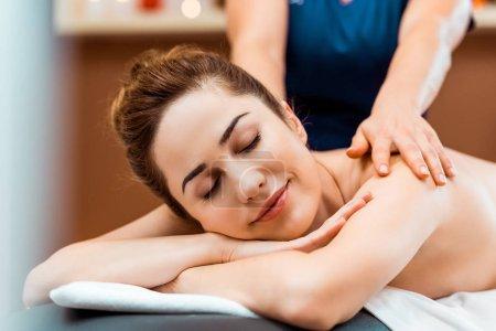 hermosa joven sonriente con los ojos cerrados disfrutando de masaje en el spa