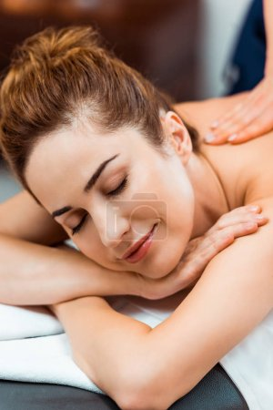 happy young woman with closed eyes enjoying massage in spa salon