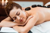 beautiful young woman with closed eyes enjoying hot stone massage in spa salon
