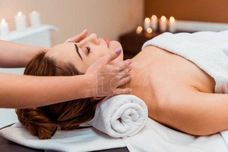 Photo pour Vue latérale de la jeune femme ayant massage facial dans le salon de spa - image libre de droit