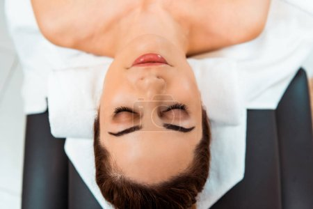 top view of beautiful young woman with closed eyes lying on massage table