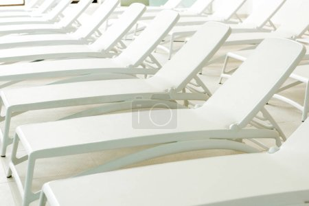 empty white sunbeds in modern spa center
