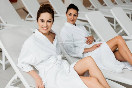 attractive young women in bathrobes resting on sunbeds and smiling at camera in spa