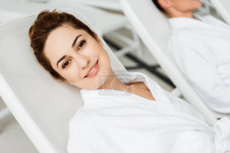 beautiful young woman smiling at camera while resting on sunbed in spa