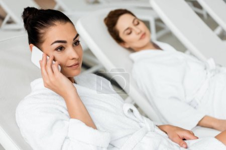 smiling young woman in bathrobe talking by smartphone while resting on sunbed in spa