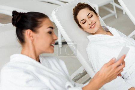 sourire des jeunes femmes en robes de chambre à l'aide de smartphone et de parler tout en vous relaxant dans le spa