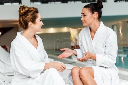 smiling young women in bathrobes talking while relaxing together in spa