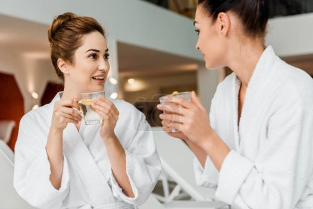 Photo for Young women in bathrobes holding cups with herbal tea and talking while resting in spa - Royalty Free Image