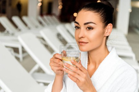 attractive young woman in bathrobe drinking herbal tea and looking away in spa