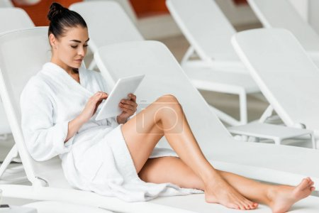 young woman in bathrobe using digital tablet on sunbed in spa