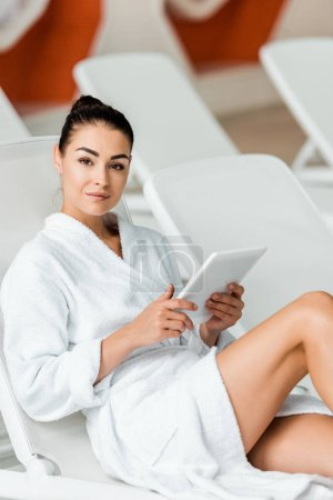 beautiful young woman in bathrobe holding digital tablet and smiling at camera in spa