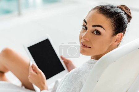 beautiful woman holding digital tablet with blank screen and looking at camera in spa