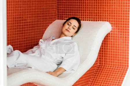 attractive young woman in bathrobe resting in spa