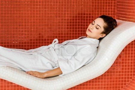 beautiful young woman in bathrobe relaxing in spa