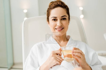 young woman in bathrobe holding cup with herbal drink and smiling at camera while relaxing in spa