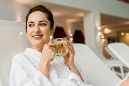 beautiful smiling young woman in bathrobe holding cup with herbal drink while relaxing in spa