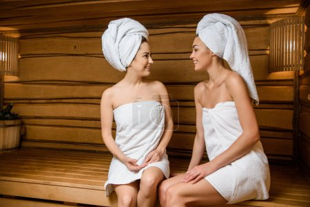 attractive young women smiling each other while relaxing together in sauna