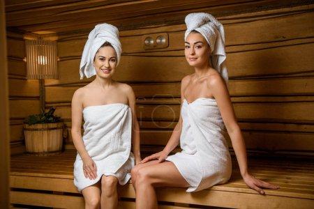 Photo pour Belles jeunes femmes souriant à la caméra tout en se relaxant ensemble dans le sauna - image libre de droit