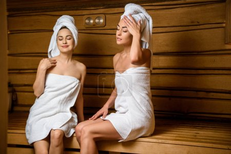 attractive young women relaxing together in steam-room