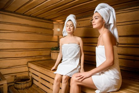 beautiful young women relaxing together in sauna