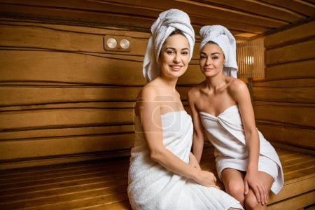 attractive young women sitting together in sauna and smiling at camera