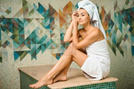 Foto de Atractiva joven en toallas mirando hacia otro lado mientras está sentada en baño turco - Imagen libre de derechos