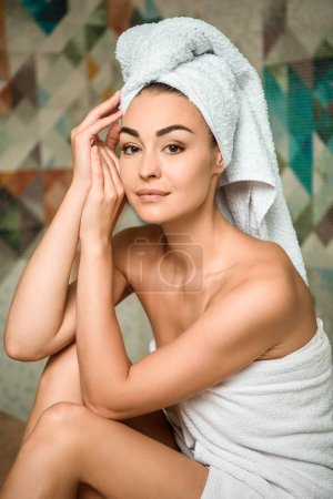 attractive young woman in towels looking at camera while sitting in turkish bath