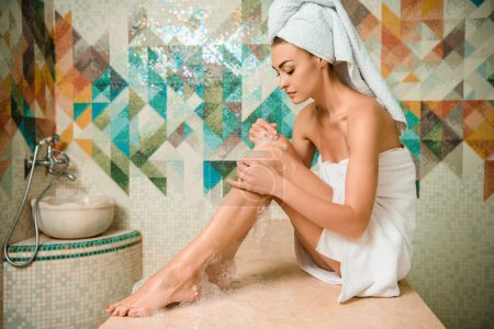attractive girl applying foam and sitting on hammam table in turkish bath