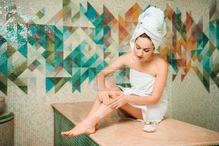 Photo pour Jeune femme appliquant gommage tout en étant assis sur la table de hammam bain turc - image libre de droit