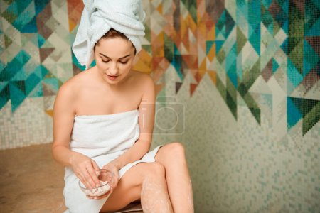 young woman holding scrub while sitting on hammam table in turkish bath