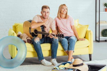 Photo pour Mari tenant la guitare tout en femme rêvant de vacances d'été et assis sur le canapé à la maison - image libre de droit