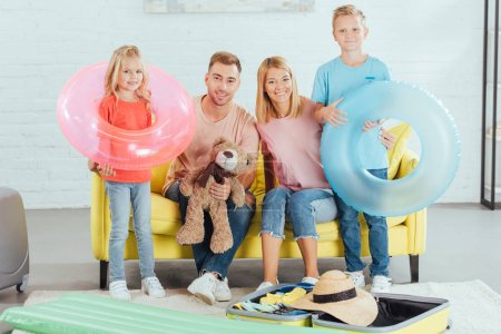 Photo for Happy family packing baggage for summer vacation, travel concept - Royalty Free Image