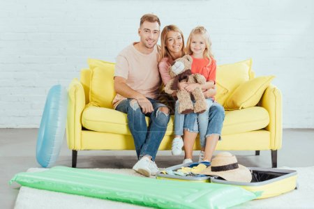 family sitting on couch and packing for family summer holiday