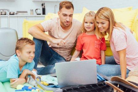 Photo pour Famille heureuse en utilisant un ordinateur portable, la planification des vacances d'été, l'emballage des bagages et d'avoir beaucoup de temps, concept de voyage - image libre de droit