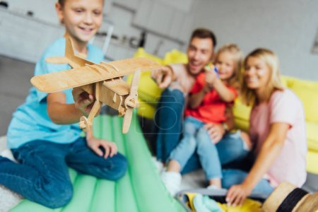 boy playing with toy wooden airplane with family having fun on background