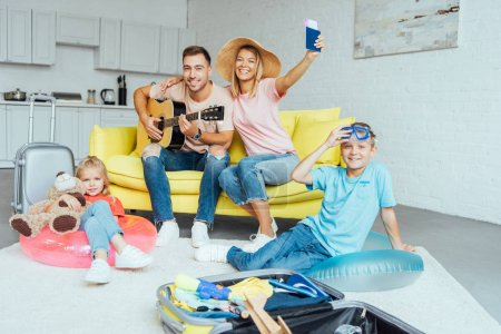 Photo pour Famille heureuse tenant passeport, bagage d'emballage pour les vacances d'été et avoir beaucoup de temps, concept de voyage - image libre de droit