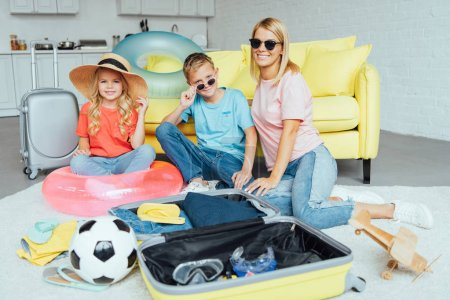 happy family packing baggage for summer vacation, travel concept