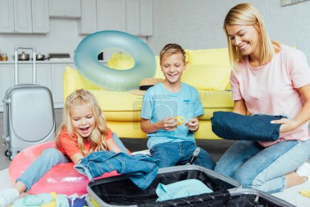 cheerful family spending time together and packing for summer vacation, travel concept