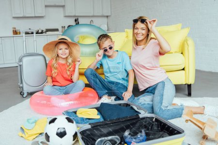 happy family trying on beach accessories and packing for summer vacation, travel concept