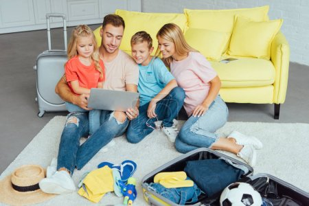 Photo for Happy family using laptop, planning summer vacation, packing luggage and having great time, travel concept - Royalty Free Image