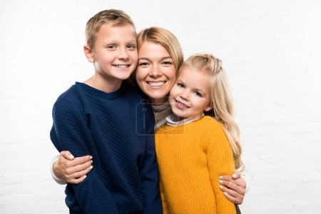 Photo for Happy mother hugging son and daughter looking at camera on white background - Royalty Free Image